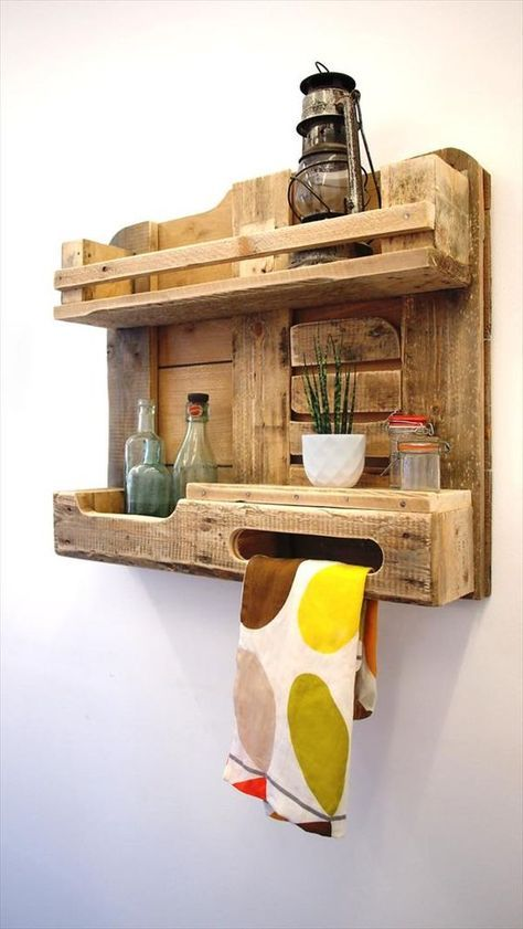 a rustic pallet kitchen shelf with a lantern, jars and bottles and even a towel holder is a cool piece