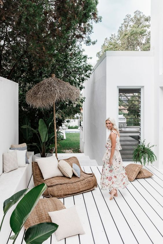 a tropical porch with a whitewashed wooden floor, burlap furniture, an umbrella, potted greenery and pillows