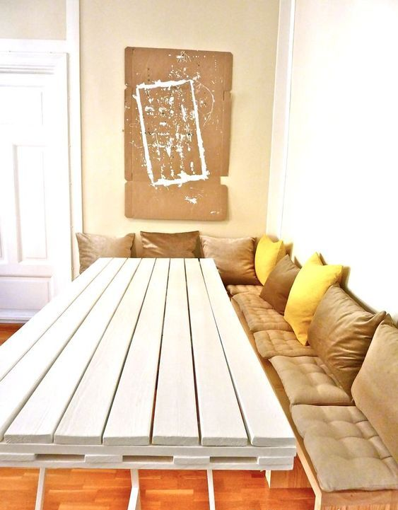 a white dining table with a tabletop made of a single pallet on thin metal legs is a bold contemporary idea