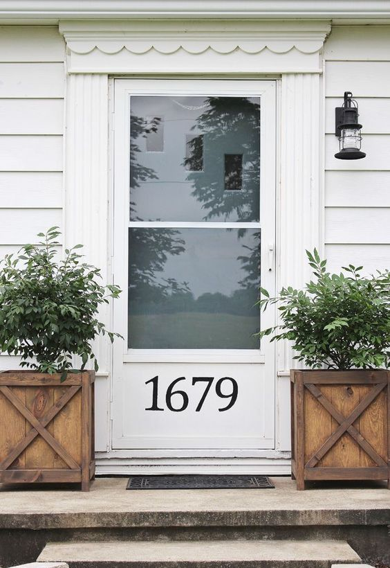 a white door with glass and a house number plus wooden planters and small trees for a vintage farmhouse feel