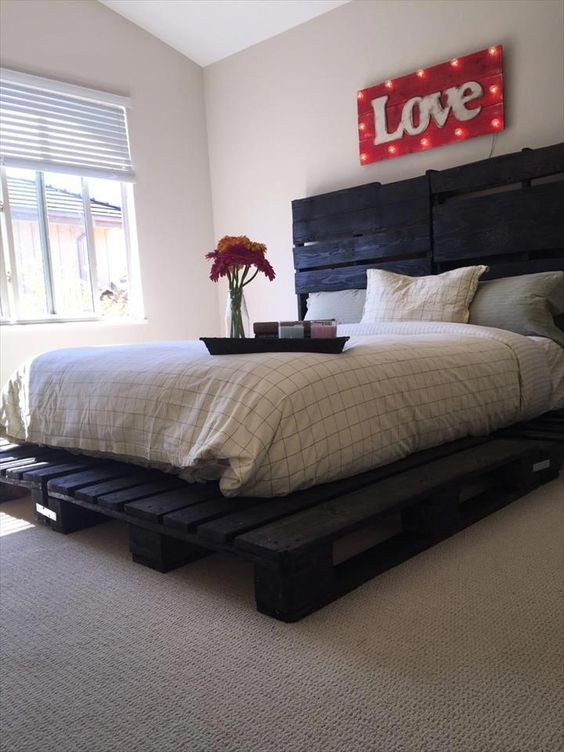 a dark painted pallet bed looks unusual and more harsh than a usual light stained one