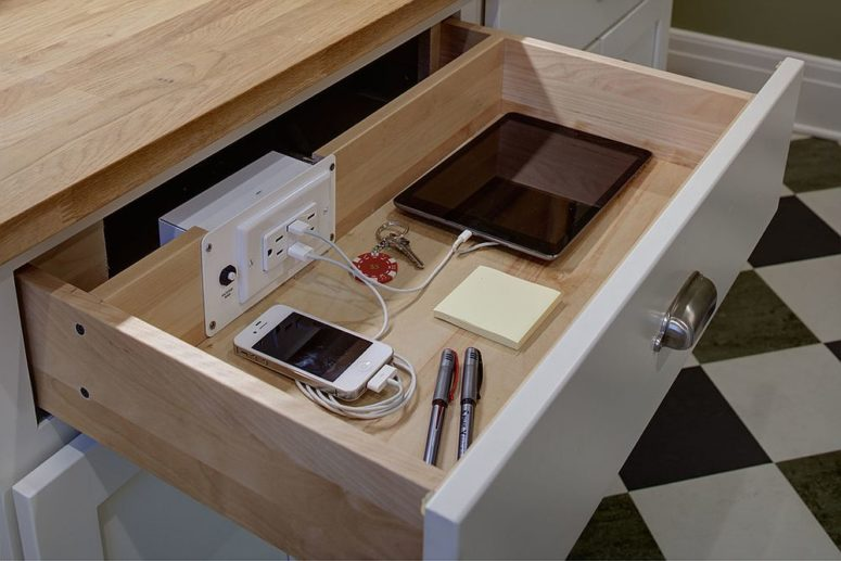 a drawer in one of the cabinets used as a charging station is a cool idea for a modern kitchen