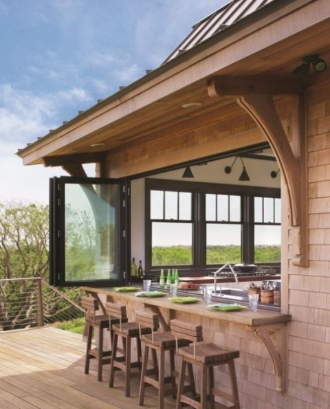 a foldable window with black framing and a light stained outdoor windowsill plus wooden chairs