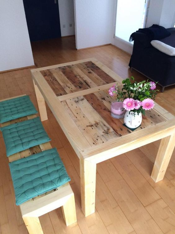 a light-colored stained dining table of pallet wood and matching benches with colorful cushions