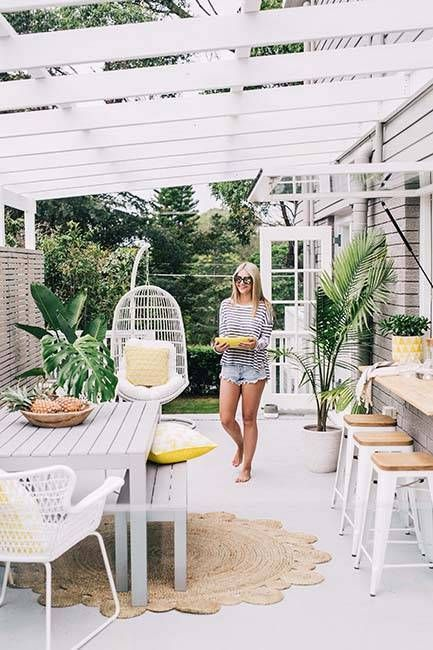 a tropical terrace with a pass through window as a bar counter and an eating space, potted plants and a rattan hanging chair for a tropical feel