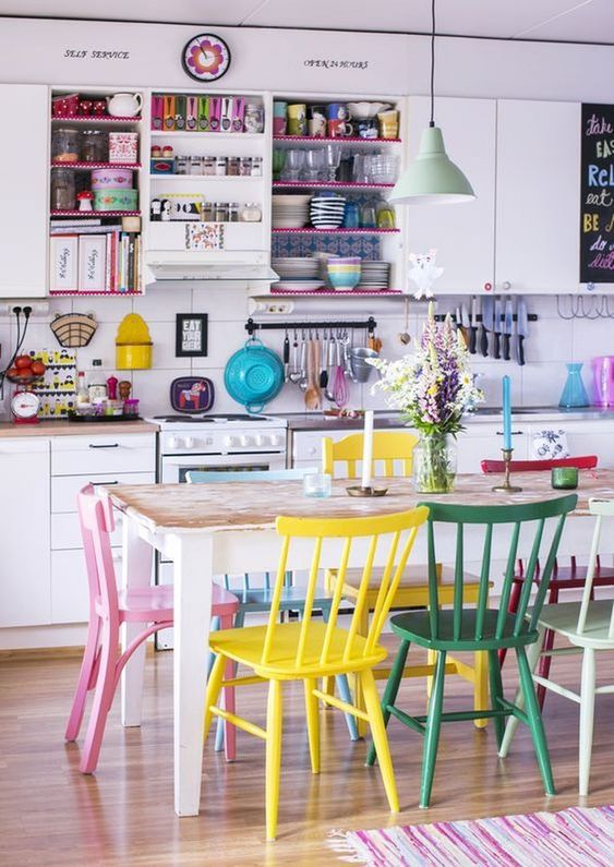 mismatching colorful chairs and colorful tableware and shelves make the space bold and cheerful