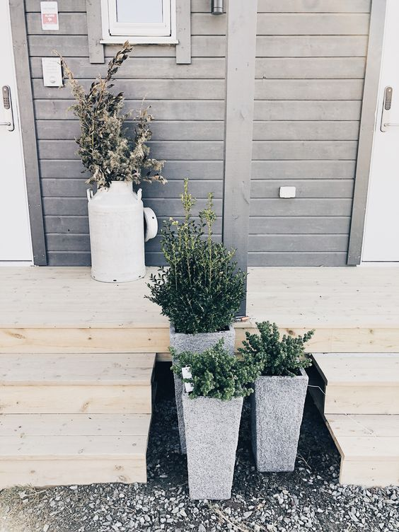 stylish concrete planters with greenery and a milk churn with some branches for a modern front yard