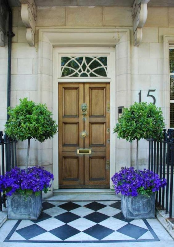 vintage box planters with bright purple blooms and trees plus a neutral wooden door
