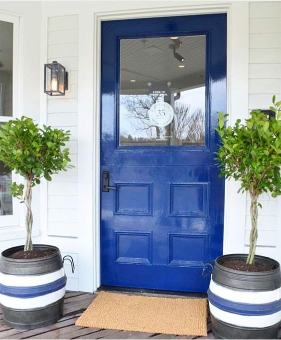 a cobalt blue front door and striped planters with small trees and a jute rug for a bright and welcoming porch