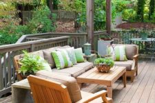 08 a cozy and welcoming summer deck with bright green and white touches and striped pillows for catchiness