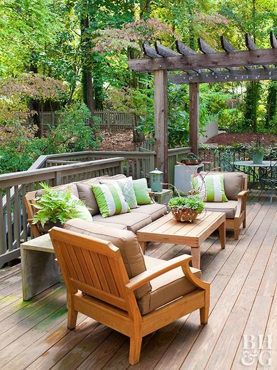 a cozy and welcoming summer deck with bright green and white touches and striped pillows for catchiness