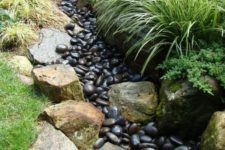 08 a dry creek bed with dark pebbles and lined up with large rocks and grasses is a cool idea