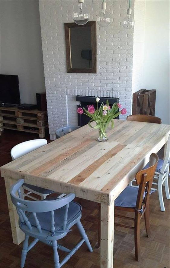 a neutral dining table of stained pallet wood and mismatching chairs for an eclectic dining space