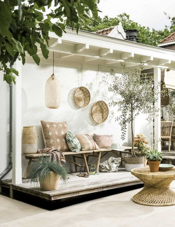 a welcoming boho tropical patio with a rattan table, a wooden bench with plenty of pillows, wicker planters and decorative baskets