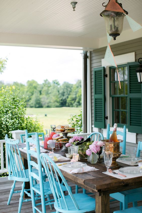mismatching blue chairs make the outdoor dining space bold and color-infused, refresh this zone