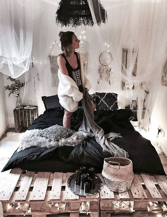a pallet bed with lights inside and over it for a boho chic bedroom, a tulle canopy over the bed makes it cooler