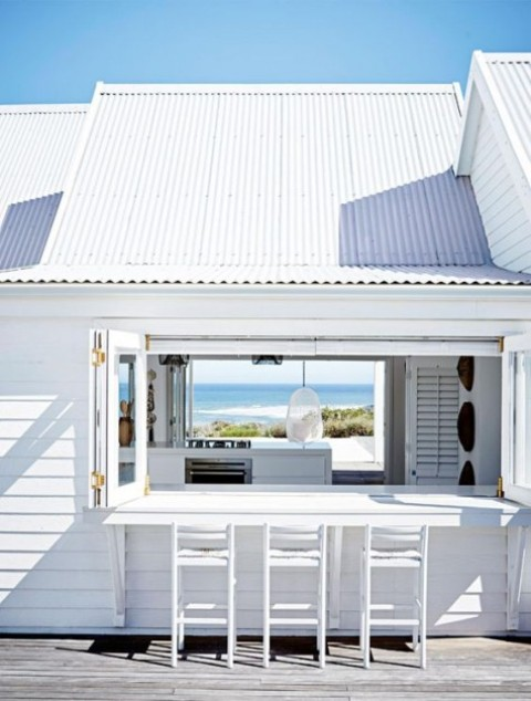 a simple white frame foldable window and a white wooden tabletop and stools for a beach home