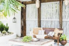09 a welcoming tropical patio with woven lanterns, a wooden beach with pillows and a vintage low table plus cacti in a flower bed