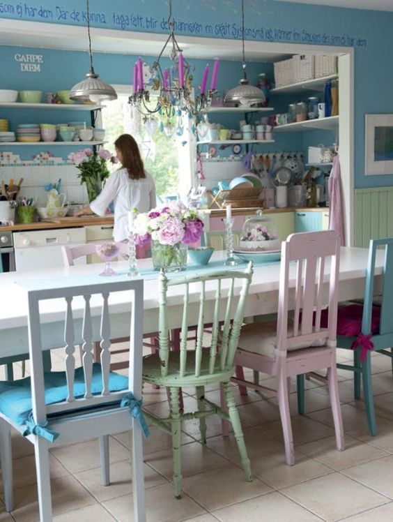 mismatching pastel chairs with colorful cushions for a colorful and eclectic dining space