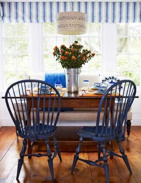 a beach-inspired dining space with navy chairs and touches of bold blue plus a printed lampshade