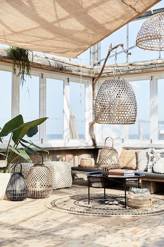 a boho chic tropical patio with a large upholstered bench, rattan and metal lanterns and a boho rug plus potted greenery