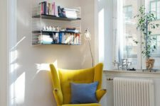 10 a mustard wingback chair with a blue pillow and a grey rug by the window is a cute idea