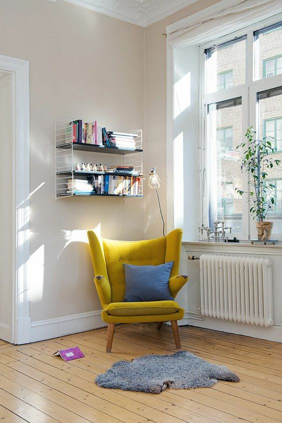 a mustard wingback chair with a blue pillow and a grey rug by the window is a cute idea