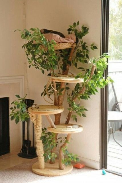 a nature-inspired cat tree with branches, plywood platforms and lots of fake greenery and jute rope