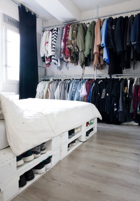 a pallet bed with storage space inside can be used to place your shoes inside   a cool idea to save some space in your bedroom
