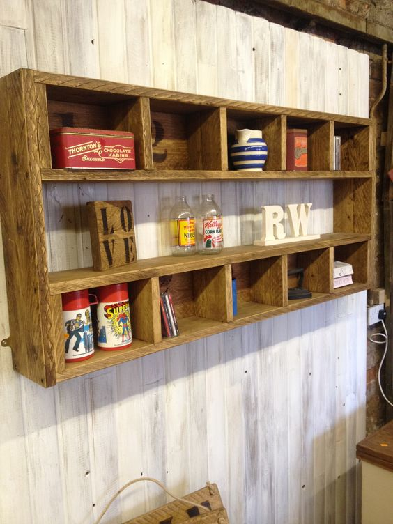 a rustic shelving unit with many compartments built of stained pallet wood is a cool DIY