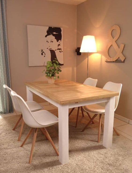 a simple indoor-outdoor dining table with a tabletop made of pallet wood and a white base plus white chairs