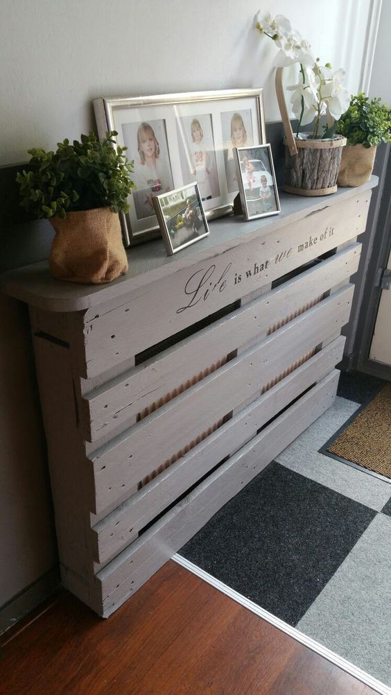 a whitewashed pallet console table doesn't only give a tabletop for storage but also hides a radiator