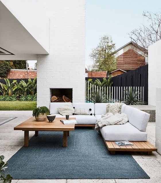 an outdoor living room with a fireplace and comfy furniture of pallets plus a cool blue rug