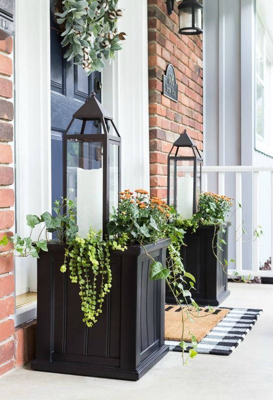 symmetrical black wooden planter boxes with greenery, blooms and large candle lanterns for farmhouse charm