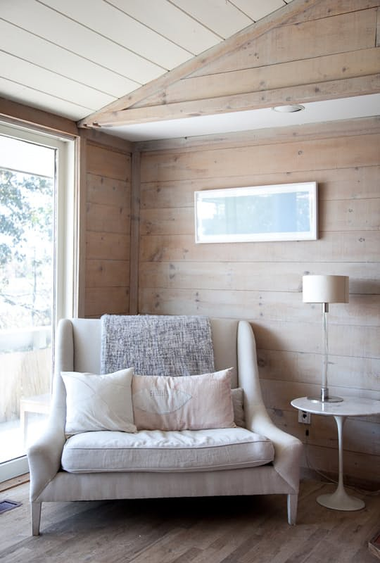 a comfy oversized neutral chair with cushions and pillows placed by the window to read cozily