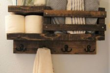 11 a rustic stained pallet shelf for a small bathroom features toilet paper storage, towel storage and even hooks for towels