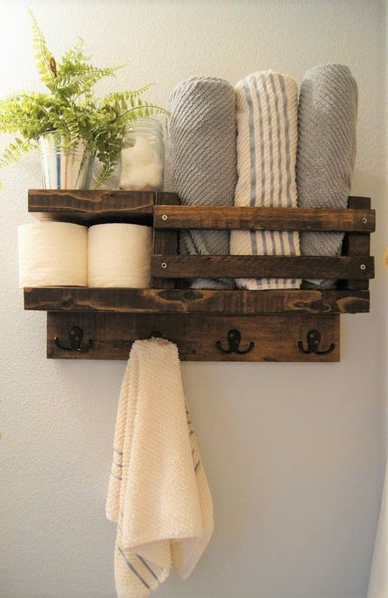a rustic stained pallet shelf for a small bathroom features toilet paper storage, towel storage and even hooks for towels