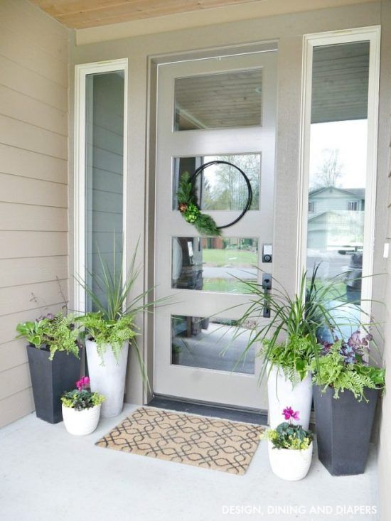 matching white and graphite grey planters with various greenery and flowers refresh and dress up the porch