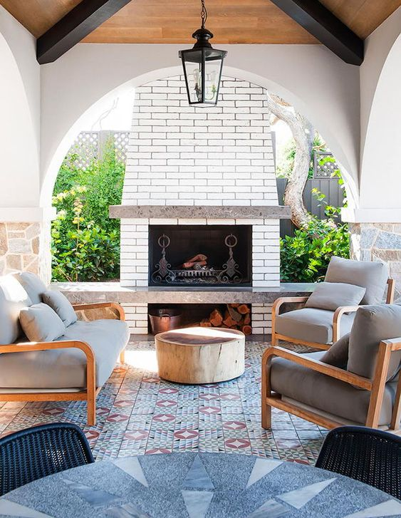 a bright outdoor lounge with a fireplace, a mosaic tile floor and a bold table plus comfy chairs