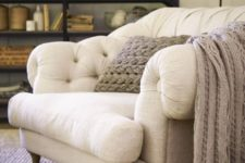 12 a gorgeous large overstuffed chair in cream, with wooden legs and a knit blanket and pillow to sink in