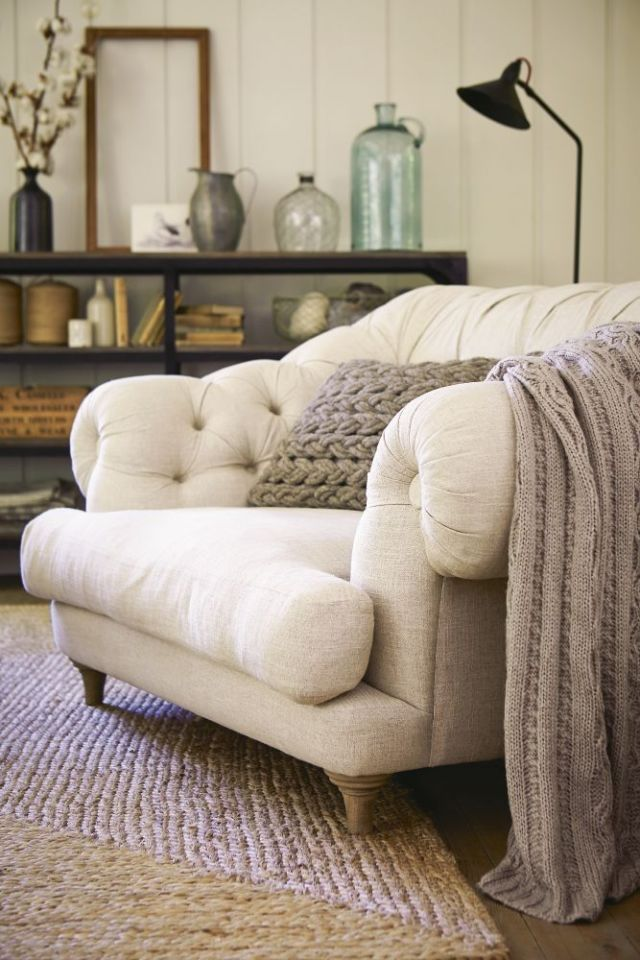 a gorgeous large overstuffed chair in cream, with wooden legs and a knit blanket and pillow to sink in