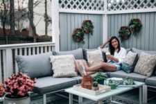 12 a grey boho deck with touches of natural green and pink blooms plus a wicker ottoman