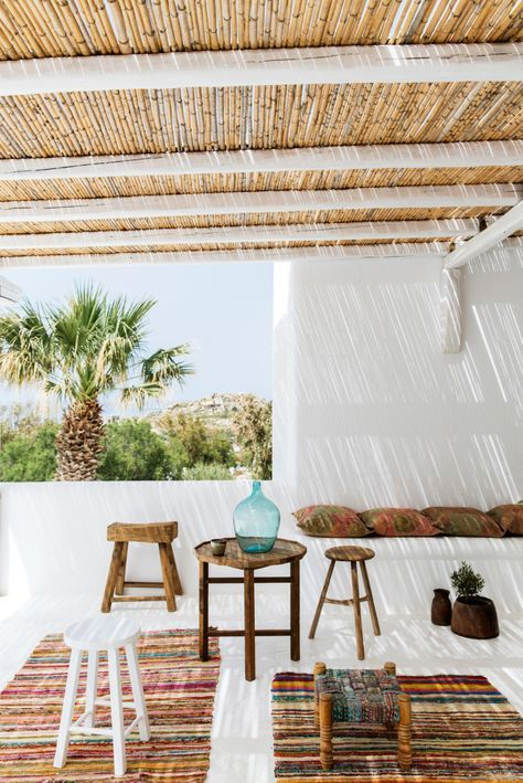 a tropical terrace with colorful boho rugs, wooden stools and a table, some pillows and potted grreenery