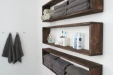 12 sleek and long wall-mounted bathroom shelves buuiltof dark sained pallet wood are ideal if you have little space
