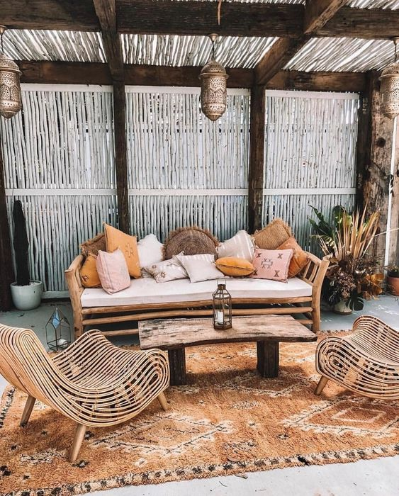 a boho tropical patio with a wooden bench and lots of pillows, catchy rattan chairs, a wooden table and a boho rug plus Moroccan lanterns