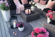 13 a bright black and blush deck with wicker furniture, blush pillows and hot pink potted blooms