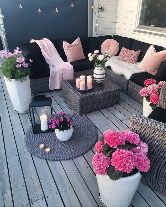 a bright black and blush deck with wicker furniture, blush pillows and hot pink potted blooms