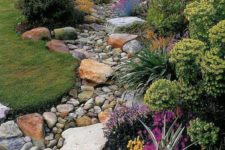 13 a dry river bed with pebbles and larger pieces of rocks and grass and bright blooms lining up