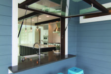 13 a garage-style dark framed window, a black tabletop and bright blue metal stools for cofy meals