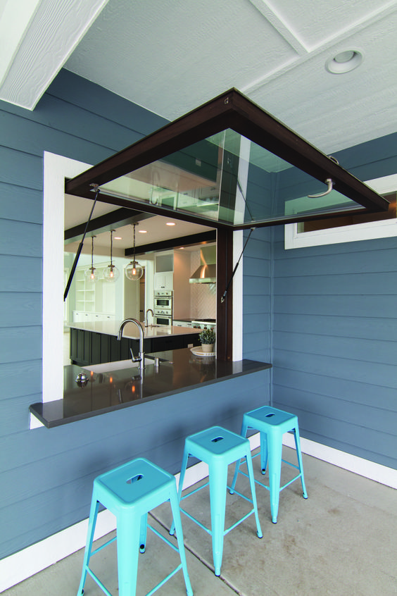 a garage-style dark framed window, a black tabletop and bright blue metal stools for cofy meals